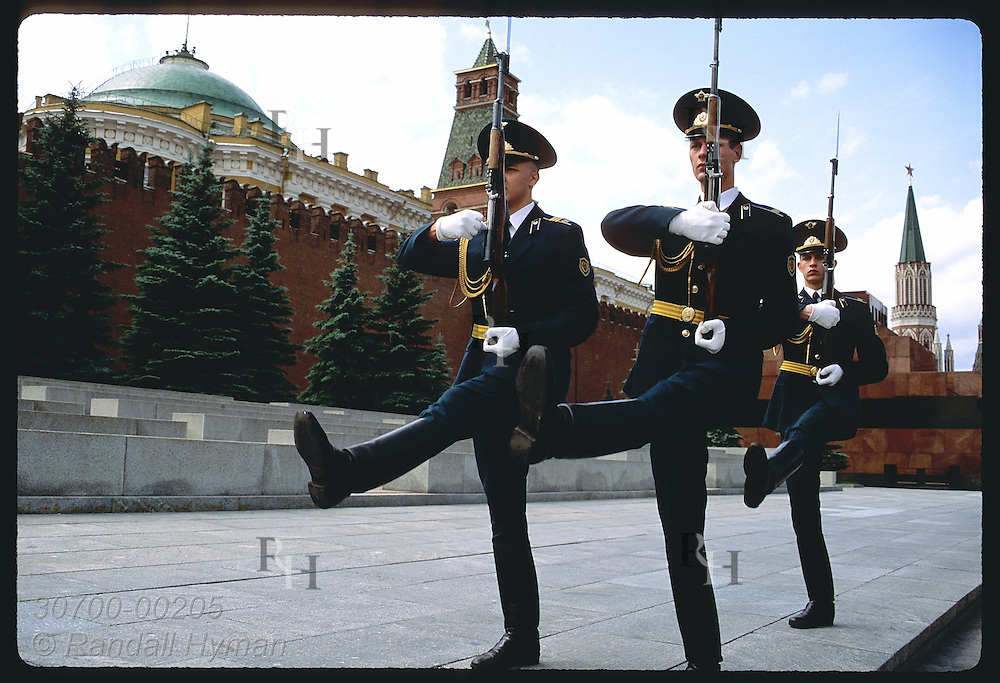 Three guards goose-step from Lenin's Tomb past the Kremlin wall on Red Square in Moscow. Russia