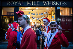 © Licensed to London News Pictures. 10/12/2016. London, UK. Santas walk past a 'Christmas Spirits' window display as thousands descend on central London for the annual Santacon Parade. Photo credit: Rob Pinney/LNP