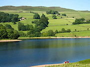 A couple relaxing on deck chairs by the water at on 17 June 2017 at Ladybower Reservoir, Derbyshire