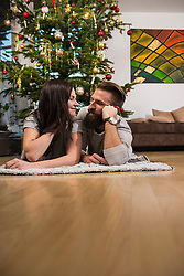 Couple lying on carpet at home