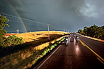 """After the Storm - Riding to the Drags in Belle Fourche, SD. 1980<br /> <br /> Limited Edition Print from an edition of 50. Photo ©1980 Michael Lichter.<br /> <br /> The Story: In 1979, there was flat track racing and hill climbs, but there was no drag strip in Sturgis.  If you wanted to see Pete Hill drag race his Knuckle, you had to ride to Belle Fourche.  It was questionable whether they would be racing on this day as the group of bikers mostly from Boulder left Sturgis' City Park campground.  Half way to the track, the skies began to clear.  A rainbow appeared just as the sun made the wet pavement and prairie grasses glow.  Free spirits crossed the """"Great West""""."""