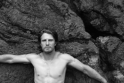 portrait of a rugged man without a shirt outdoors against rock formation