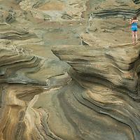 A Tourist snaps a photo amidst eroded sandstone rocks on the southeastern coast of Oahu, Hawaii;