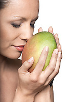 Closeup portrait of beautiful woman smelling fresh mango with eyes closed in studio isolated on white background
