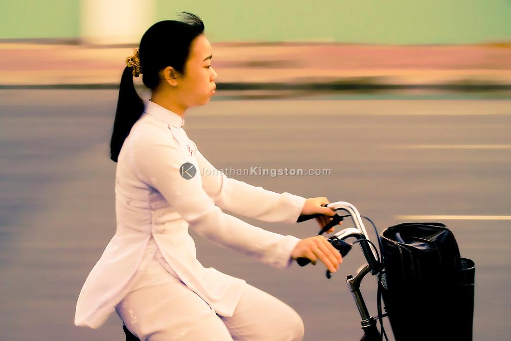 Adult woman bike commuter, Ho Chi Minh city, Vietnam.