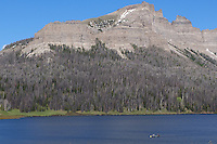 Boaters paddle along Brooks Lake beneath the Pinnacle Buttes near Togwotee Pass in the Shoshone National Forest.