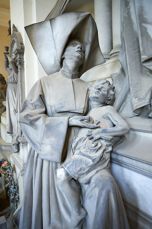 """Picture and image of the stone sculptures of angels and a Sister of Charity. in memory of the surgeon Luigi Pastorini, the sculptor Navone has conceived a complex allegory, in which a feminine winged figure, representing the Medicine, distributes some wealth to a Sister of Charity who holds an ill baby. She is helped by another winged figure, the Munificence, whose regard is turned towards the deceased. The """"Cappellone"""" Sisters – they are so named because of their large head covering – were so committed to provide aid to the poor that they have become the symbol of the assistance to the needy. Navone has succeeded in harmonizing the Medicine allegory and its delicacy with the raw representation of the poor people: in fact, as from the middle years of the bourgeois realism, the poor were portrayed in a very realistic way, without any idealization. Sculpted by G. Navone 1902. Section A, no 28,  The monumental tombs of the Staglieno Monumental Cemetery, Genoa, Italy .<br /> <br /> Visit our ITALY PHOTO COLLECTION for more   photos of Italy to download or buy as prints https://funkystock.photoshelter.com/gallery-collection/2b-Pictures-Images-of-Italy-Photos-of-Italian-Historic-Landmark-Sites/C0000qxA2zGFjd_k<br /> If you prefer to buy from our ALAMY PHOTO LIBRARY  Collection visit : https://www.alamy.com/portfolio/paul-williams-funkystock/camposanto-di-staglieno-cemetery-genoa.html"""