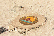 A drain manhole cover on the beach at Puerto Baquerizo Moreno with a picture of León Dormido or Kicker Rock and the words 'Gobierno Municipal de San Cristobal',  Municipal Government of San Cristobal.   Puerto Baquerizo Moreno, San Cristobal, Galapagos, Ecuador