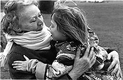 Elderly woman hugging young girl,