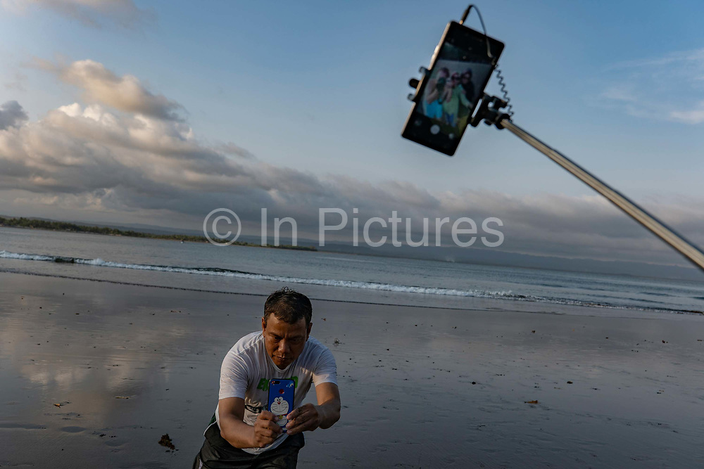 A man takes a picture using a mobile phone while his subject holds a selfie stick to take a selfie at Batu Karas beach on the 31st October 2019 in Java in Indonesia.