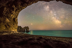 © Licensed to London News Pictures. 16/6/2018. Lulworth, UK. A long exposure highlights The Milky Way, framed by a cave, in sight of Durdle Daw at Lulworth in Dorset. Photo credit: Peter Scott/LNP
