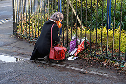 A woman stops to look at flower tribute left at scene of teenager's fatal stabbing in Chelmsford December 2014 Essex.