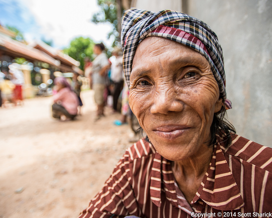 A woman waits outside New Hope School for her monthly allotment of rice from New Hope School in Siem Reap, Cambodia.