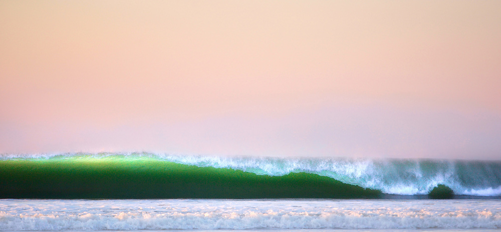 Green offshore wave breaking with a pink sky at sunset at St Ouen's Bay, Jersey, C.I.