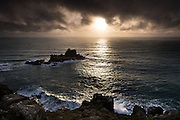 Land's End in a Winter sunset. Short bursts of sunlight under blankets of winter storm clouds. Deceptively calm seas nevertheless created large waves as swell reached the cliffs.
