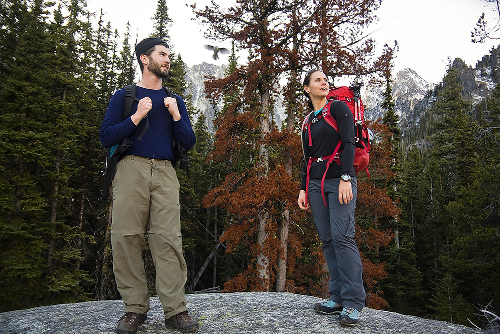 Dallas Anderson and Grace Marx stand on a large boulder as a gray jay takes flight in the background, Alpine Lakes Wilderness, Washington.