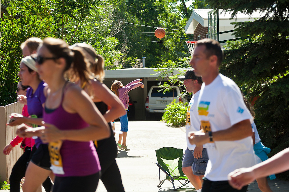 A girl throws a basketball as competitors run past in the 2012 Bolder Boulder 10K road race in Boulder, Colorado.