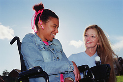 Care manager and young woman with Cerebral Palsy talking and smiling together in park,