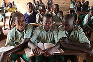 Michael Owino, 12, center, at Rabango Primary School. Michael shares his home with his four brothers in Homa Bay, Kenya. Michael was 3 when he lost his mother to complications from AIDS a year after his father passed away from the same disease. The Kenyan district of Nyanza incidence of HIV and many children have been orphaned as a result. Many are forced to drop out of school due to an inability to purchase uniforms or pay a modest school fee. The Owino brothers receive support from The Child Behind Project, which assists Orphans and Vulnerable Children (OVC) in the area. They receive help with school fees, uniforms, medical care, blankets, grains, and thrice monthly visits from a community health worker. Sara A. Fajardo/Catholic Relief Services