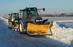 © Licensed to London News Pictures. 26/01/2013..North Yorkshire Moors, England..Two tractors clear snow from a road following heavy overnight snowfall on the North Yorkshire moors...Photo credit : Ian Forsyth/LNP