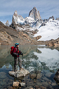 """Mount Fitz Roy (3405 m or 11,171 ft elevation) reflects in Laguna de Los Tres in Los Glaciares National Park, Santa Cruz Province, Argentina, Patagonia, South America. The trail called Sendero Fitz Roy leads from El Chalten to Laguna de Los Tres (20 km round trip with 1100 meters gain). Monte Fitz Roy is also known as Cerro Chaltén, Cerro Fitz Roy, or Mount Fitz Roy. The first Europeans recorded as seeing Cerro Fitz Roy were the Spanish explorer Antonio de Viedma and his companions, who in 1783 reached the shores of Viedma Lake. In 1877, Argentine explorer Francisco Moreno saw the mountain and named it Fitz Roy in honour of Robert FitzRoy who, as captain of HMS Beagle, had travelled up the Santa Cruz River in 1834 and charted large parts of the Patagonian coast. Mt Fitz Roy was first climbed in 1952. Cerro is a Spanish word meaning hill, while Chaltén comes from a Tehuelche word meaning """"smoking mountain"""", due to clouds that usually form around the peak.  Los Glaciares National Park and Reserve are honored on UNESCO's World Heritage List. To license this Copyright photo, please inquire at PhotoSeek.com."""