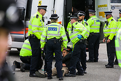 London, UK. 6 September, 2019. Metropolitan Police officers arrest a climate activist who had locked himself to another activist in one of the main access roads to ExCel London on the fifth day of a week-long carnival of resistance against DSEI, the world's largest arms fair. The road remained blocked for several hours. The fifth day of protests was themed as Stop The Arms Fair: Stop Climate Change in order to highlight links between the fossil fuel and arms industries.