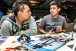 IRVINE, CA - MARCH 2: Student Eduardo Morales(R) talks to a fellow student while creating collages from magazines clips at the Treasure Room during the Working Wardrobes Dream Girls & Distinguished Gentlemen 2013 event at the Irvine Hilton in Irvine, CA. Working Wardrobes (http://www.workingwardrobes.org) is a non-profit organization located in Costa Mesa, CA. PHOTO: © 2013 SILVEX.PHOTOSHELTER.COM.