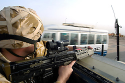 British soldier wearing desert camouflage, Kevlar helmet and body armor, carrying SA80 assault rifle which is fitted with SUSAT sights,  travels in top cover position on an armored Land Rover patrol vehicle, also known as a snatch, inf Basra during Op-Telic in March 2005
