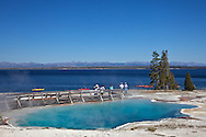 Black Pool hot spring at West Thumb Geyser Basin. Yellowstone Lake and the Absaroka Mountains are in the distance.