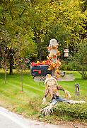 Fall season decoration of scarecrow and red leaves on mailbox.