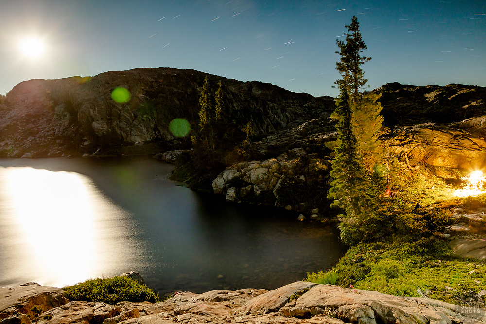 """""""Lake in the Tahoe Back Country 4"""" - Night time photograph of a small lake with no name in the Tahoe area back county, somewhat near Jackson Meadows. The moon can be seen in the shot and a small light from camp can be seen on the right."""