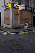 A boarded up central London mini cab business and an End of works triangle sign on a Holborn corner.