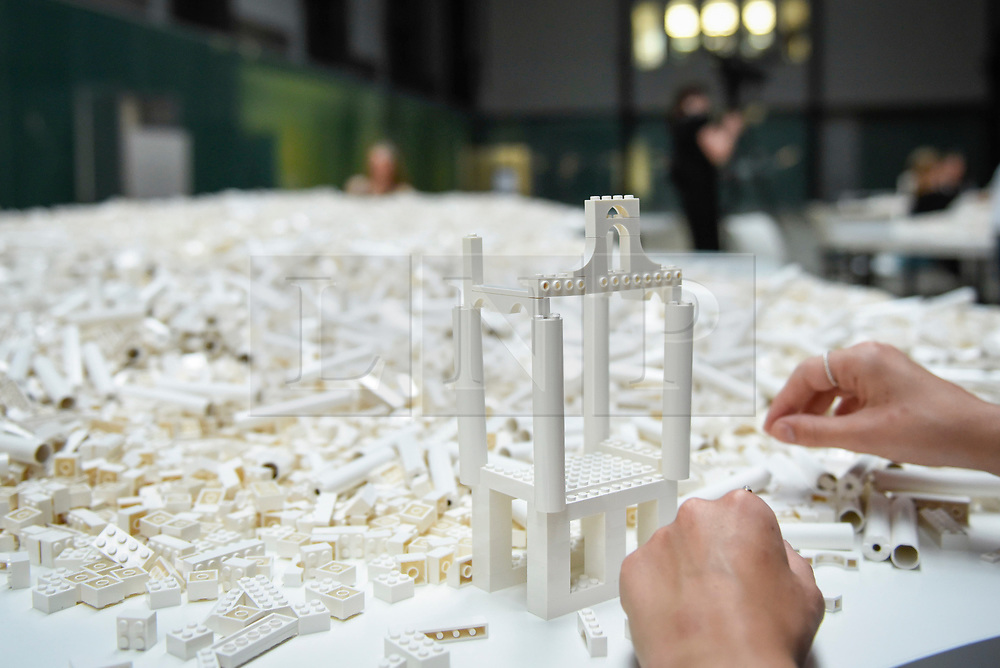 """© Licensed to London News Pictures. 26/07/2019. LONDON, UK.  A visitor works with Lego at the preview of """"The cubic structural evolution project"""", 2004, by Olafur Eliasson at Tate Modern.  Exhibited for the first time in the UK, the artwork comprises one tonne of white Lego bricks inspiring visitors to create their own architectural vision for a future city and is on display until 18 August 2019.  The work coincides with the artist's new retrospective exhibition """"In real life"""" at Tate Modern on display to 5 January 2020.  Photo credit: Stephen Chung/LNP"""