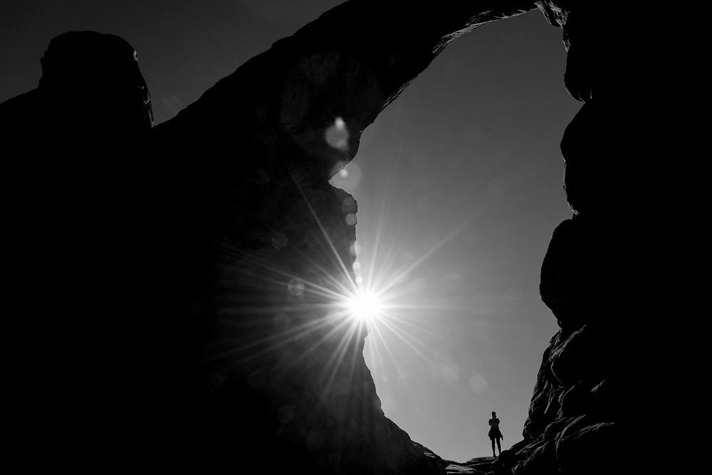 A hiker standing in Turret Arch at Arches National Park, Utah, USA.