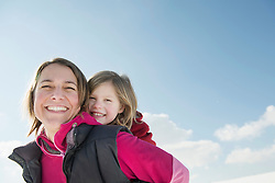 Mother giving piggyback ride to daughter, smiling, Bavaria, Germany