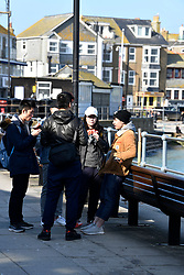 © Licensed to London News Pictures. 22/03/2020. St. Ives, UK. Tourists in St Ives. Business in the holiday town of St Ives has shut its doors to visitors in response to the Corona Virus pandemic. Photo credit: MARK HEMSWORTH/LNP