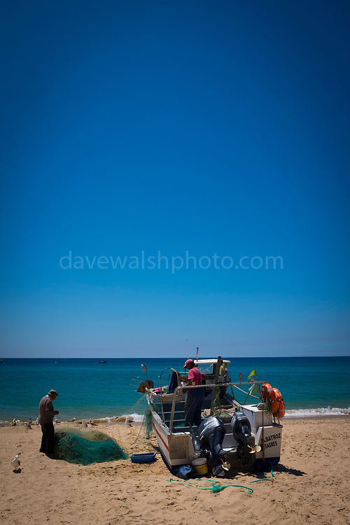 Small-scale fishermen cleaning their nets, in Salema, Algarve, Portugal.