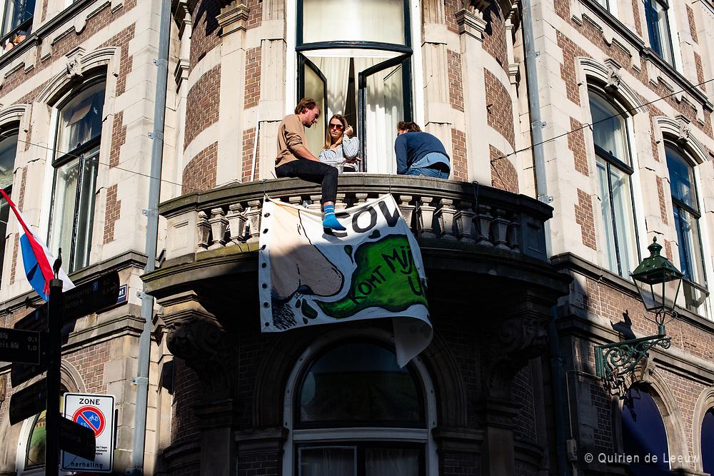 """Bewoners in Den Haag vieren bevrijdingsdag op het balkon met spandoek. """"COVID-19 komt je neus uit"""""""
