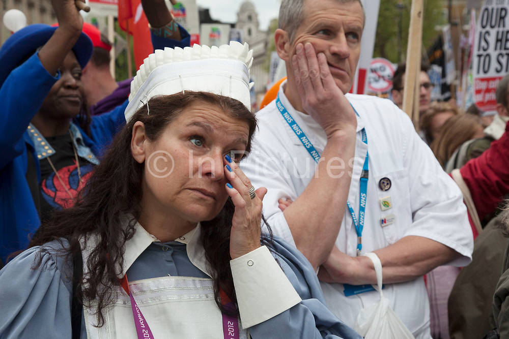 London, UK. Saturday 18th May 2013. Protestors listen to speakers during a demonstration against NHS reform and proposed funding cuts for services within the National Health Service. This woman cries as she hears of what will happen inn the future.