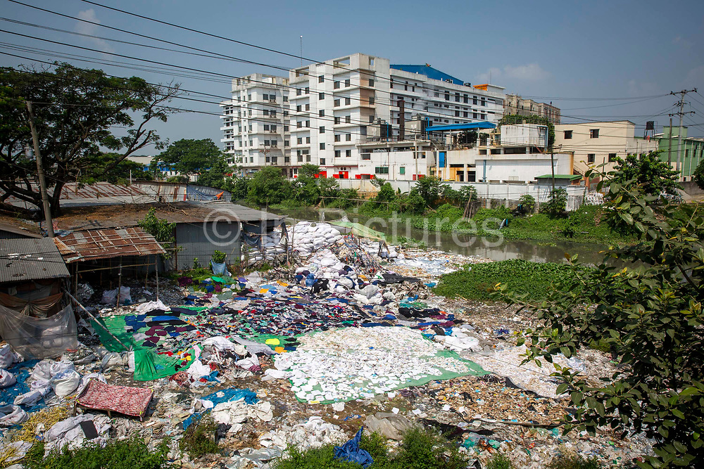 Environmental pollution on the river banks surrounding some of the textile industry buildings of Savar Upazila on 30th September 2018 in Dhaka, Bangladesh. Here a community living next to the garment industries sort and grade through large piles of discarded textiles. The garment business is the main industry of Savar Upazila, a district in the northern part of Dhaka.