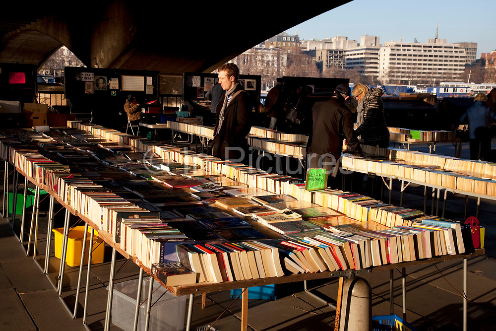 Second hand book stalls under Waterloo Bridge, Southbank, London. Every day the books are laid out on these tables and in the evening the light illuminates them in the dark under the bridge.