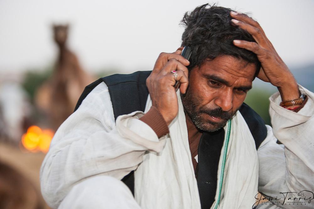 A camel trader at the Pushkar camel fair talking on a cell phone looking distraught, Pushkar, Rajasthan, India