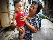 16 MAY 2017 - BANGKOK, THAILAND: A woman and a neighbor's child in Pom Mahakan. The final evictions of the remaining families in Pom Mahakan, a slum community in a 19th century fort in Bangkok, have started. City officials are moving the residents out of the fort. NGOs and historic preservation organizations protested the city's action but city officials did not relent and started evicting the remaining families in early March.           PHOTO BY JACK KURTZ