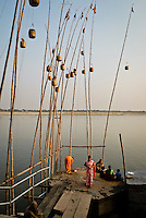 An Indian family finishes breakfast and bathing rituals on the banks of the River Ganges in Varanasi, Uttar Pradesh, India