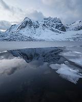 Stjerntind mountain peak rises above partially frozen water of lake Storvatnet, Flakstadøy, Lofoten Islands, Norway