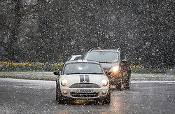 © Licensed to London News Pictures. 26/02/2018. Oxshott, UK. Traffic is seen as snow falls as cold front sweeps in from the east - with heavy snow expected later in the week in parts of the UK. Photo credit: Peter Macdiarmid/LNP
