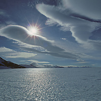 Sun and Lenticular clouds over a bare ice glacier near the Patriot Hills in Antarctica's southern Ellsworth Mountains.