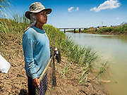 01 JULY 2015 - PA TAN, LOPBURI, THAILAND:  A rice farmer does some subsistence fishing in an irrigation canal in Lopburi province. Normally the canal is too full of fast flowing water for the farmers to fish in it. One farmer said nobody in their community could remember the canal ever being this low. Central Thailand is contending with drought. By one estimate, about 80 percent of Thailand's agricultural land is in drought like conditions and farmers have been told to stop planting new acreage of rice, the area's principal cash crop. Water in reservoirs are below 10 percent of their capacity, a record low. Water in some reservoirs is so low, water no longer flows through the slipways and instead has to be pumped out of the reservoir into irrigation canals. Farmers who have planted their rice crops are pumping water out of the irrigation canals in effort to save their crops. Homes have collapsed in some communities on the Chao Phraya River, the main water source for central Thailand, because water levels are so low the now exposed embankment is collapsing. This is normally the start of the rainy season, but so far there hasn't been any significant rain.    PHOTO BY JACK KURTZ