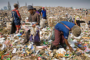 """25 FEBRUARY 2008 -- MAE SOT, TAK, THAILAND: Burmese migrant workers go through garbage in the dump in Mae Sot, Thailand. Hundreds of Burmese migrants eke out a living in the dump going through the garbage to sell what they find. There are millions of Burmese migrant workers and refugees living in Thailand. Many live in refugee camps along the Thai-Burma (Myanmar) border, but most live in Thailand as illegal immigrants. They don't have papers and can not live, work or travel in Thailand but they do so """"under the radar"""" by either avoiding Thai officials or paying bribes to stay in the country. Most have fled political persecution in Burma but many are simply in search of a better life and greater economic opportunity.  Photo by Jack Kurtz"""