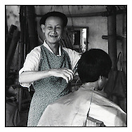 Hairdresser cuts hair in Bao Lac market, a city of northern Vietnam in Cao Bằng Province, Southeast Asia. He wears béret, traditional french headgear.